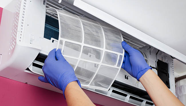 Air conditioner cleaning. Man in gloves checks the filter